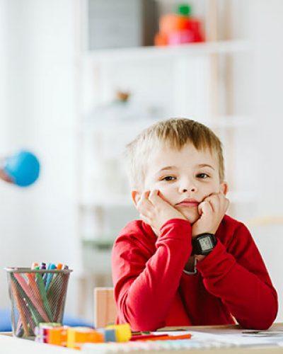 Un bambino con la testa appoggiata sulle mani